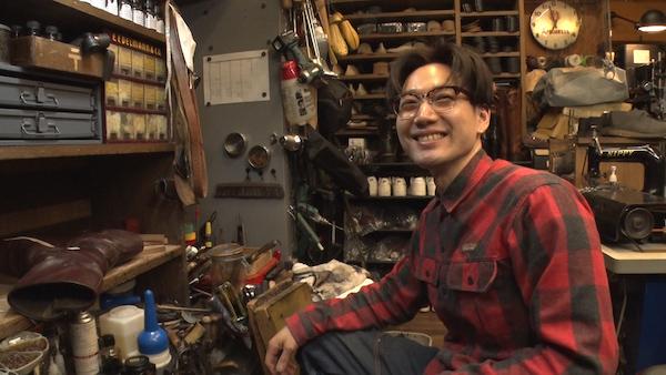 修理道具に囲まれる村上さんの画像